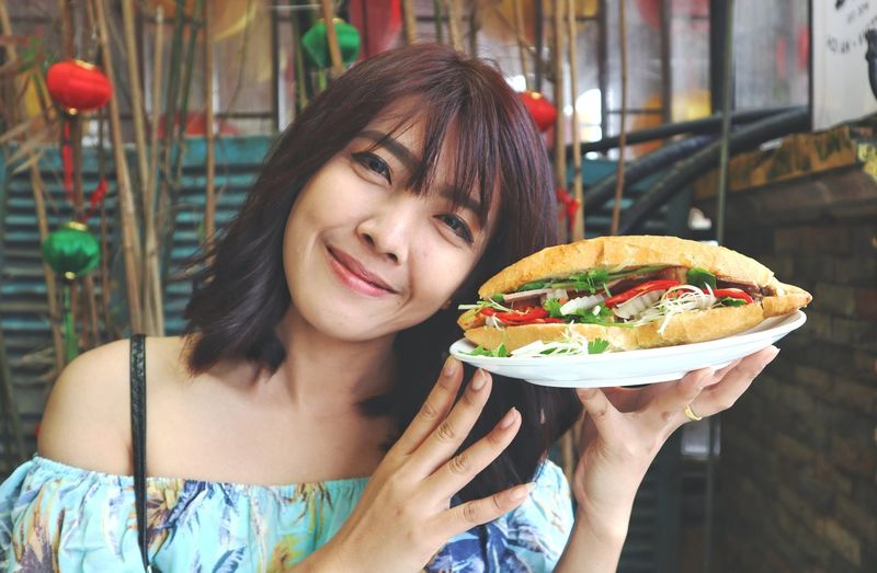 Woman showing fresh sandwich on white plate. Thai ASIA Appetizer Sandwich Organic Salad Smiling Holding Lifestyles Lunch Happy Restaurant Showing Vegetable Vegetarian Food Tasty Plate Meal Lunch Delicious Young Women Human Hand Portrait Mexican Food Smiling Women Happiness Eating Fast Food