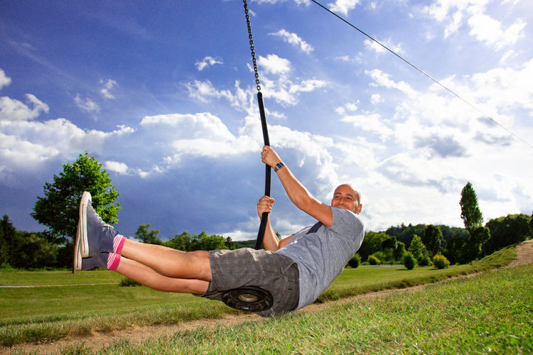 Man Sitting On Zip Line Over Field Against Sky