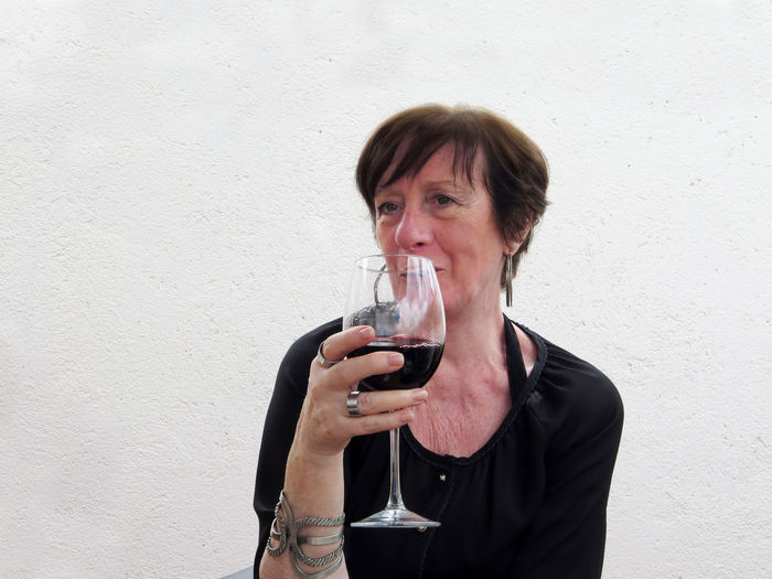Woman holding wineglass while sitting against wall