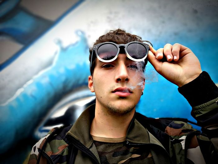 Portrait of young man smoking while wearing sunglasses