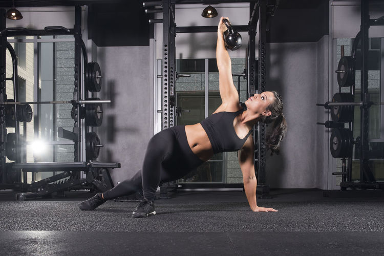 Young Woman Exercising With Kettlebell At Gym