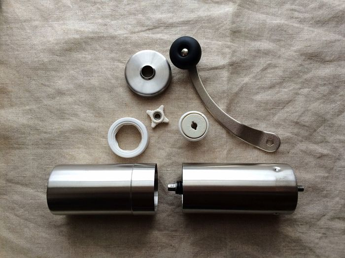High Angle View Of Coffee Hand Grinder Parts On Fabric
