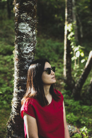 Beautiful Woman By Tree Trunk In Forest