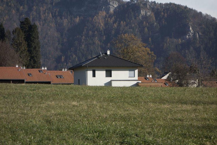 House on field by trees and mountains