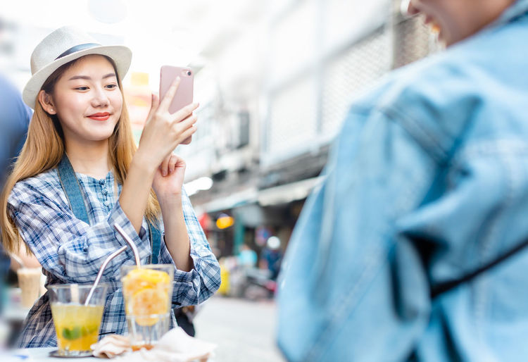 Portrait of smiling woman holding mobile phone outdoors