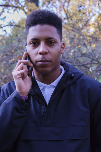 Portrait Of Young Man Talking On Mobile Phone While Standing Against Trees