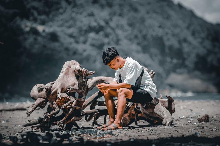 Full length of man sitting on driftwood at land
