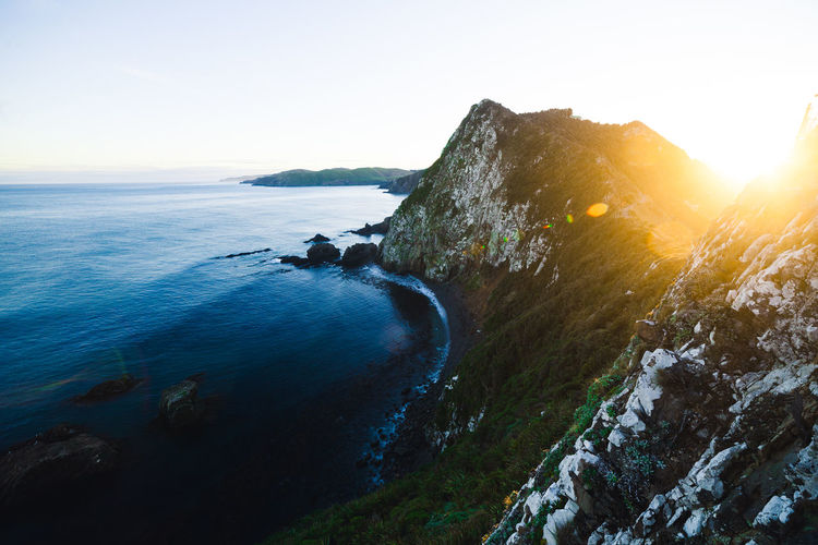 Flowing Water Lighthouse Nature Rock Sunlight Tranquility Beauty In Nature Cliff Environment Landscape Lens Flare Mountain No People Non-urban Scene Outdoors Rock - Object Scenics - Nature Sea Sky Solid Sunset Tranquil Scene Water