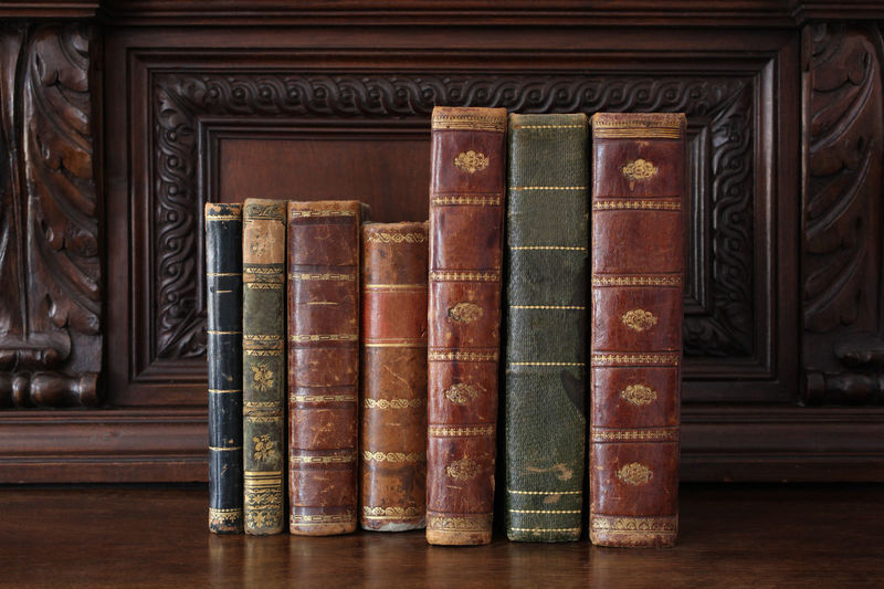 old books piled on a wooden table Antique Books Bookshelf Bookshelfs Horizontal Learning Library Read Reading Book Close Up Collection Cover Culture Indoors  No People Old Piled Reading A Book Traditional Wood - Material