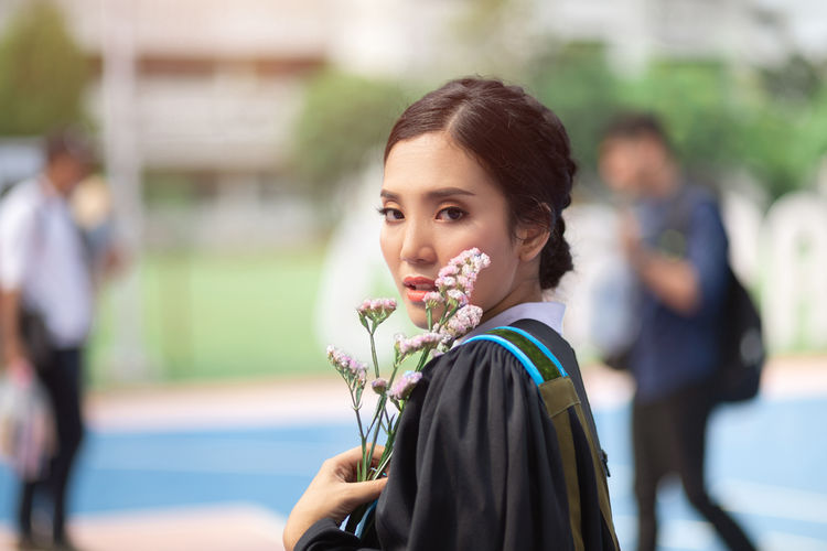 Portrait of young woman wearing graduation gown holding flowers
