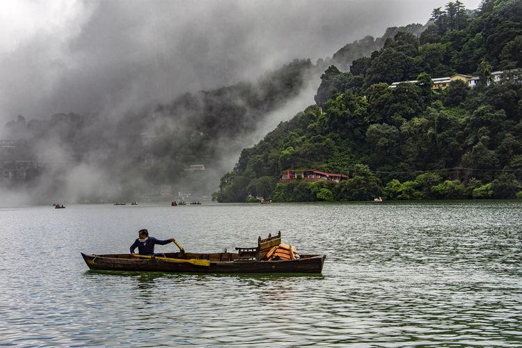 People in boat on lake against sky
