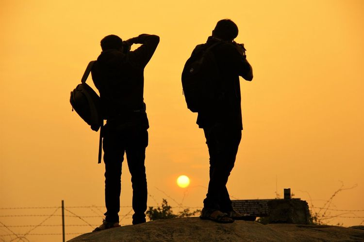 Silhouette Men Standing Against Orange Sky