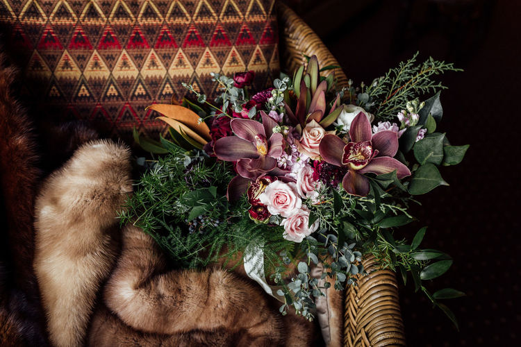 High Angle View Of Bouquet And Fur On Wicker Chair At Home