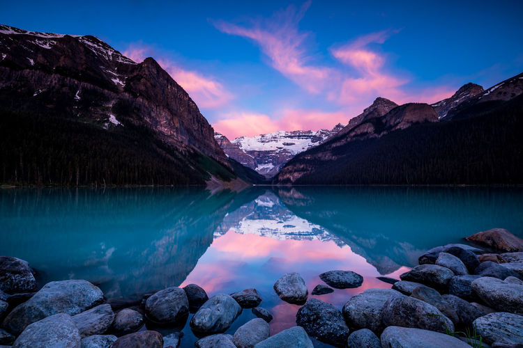 Beautiful Lake Louise During Twilight. In the Rocky Mountains of Alberta Canada, Banff National Park Scenics - Nature Water Tranquil Scene Beauty In Nature Mountain Sky Tranquility Lake Rock Rock - Object Cloud - Sky Idyllic Non-urban Scene Nature Mountain Range Reflection Blue No People Outdoors Snowcapped Mountain Formation Twilight Sunrise
