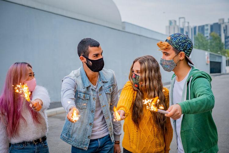 Friends wearing mask holding sparkler standing on road