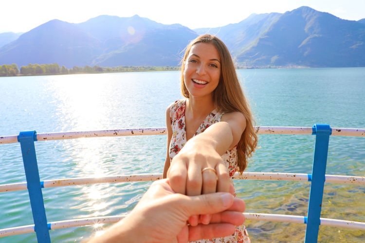 Cropped Image Of Boyfriend Holding Girlfriend Hand Against Lake And Mountains During Sunny Day