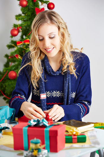 Smiling mid adult woman opening gift while sitting on table at home