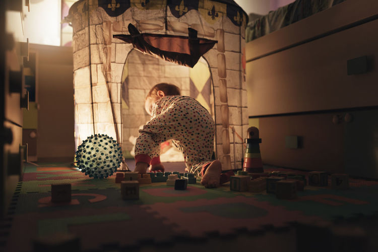 Boy Playing By Illuminated Castle In Room At Home