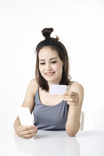 Thai Studio Shot 30-34 Years Shopping Online  Young Female Happy Asian  Laptop Beautiful Internet Attractive Smile person Computer People Portrait Holding Phone Beauty Mobile Pretty Technology Payment Adult Using Lifestyle Cheerful Purchase Business Wireless Lady Chinese Fashion Looking Smartphone Japanese  Korean Credit Card Empty Text Copy Space White Background One Person Front View Indoors  Cut Out Waist Up Young Adult Looking At Camera Young Women Smiling Hair Teeth Women Happiness Hairstyle Paper
