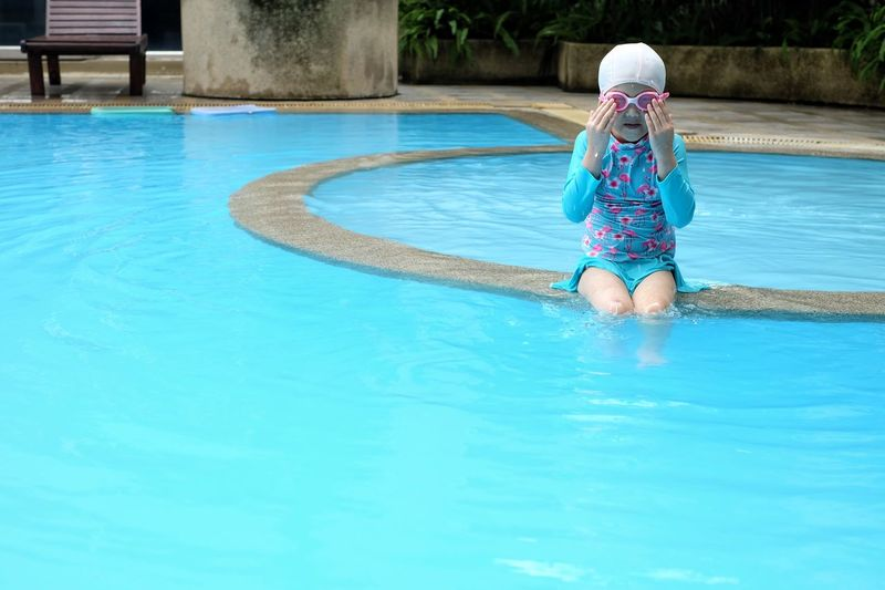 Girl Wearing Goggles While Sitting In Swimming Pool