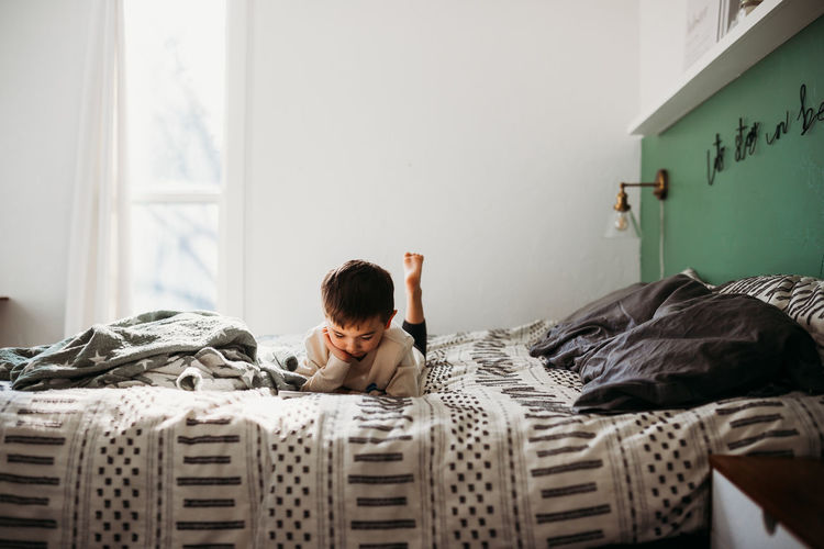 Boy relaxing on bed at home