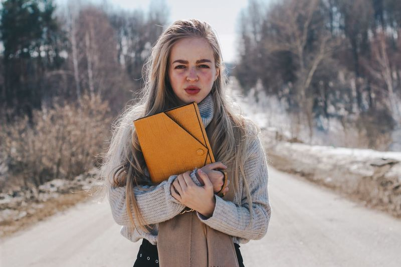 Portrait of beautiful young woman holding file while standing on road in winter