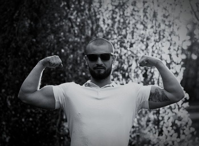 Portrait of young man flexing muscles outdoors