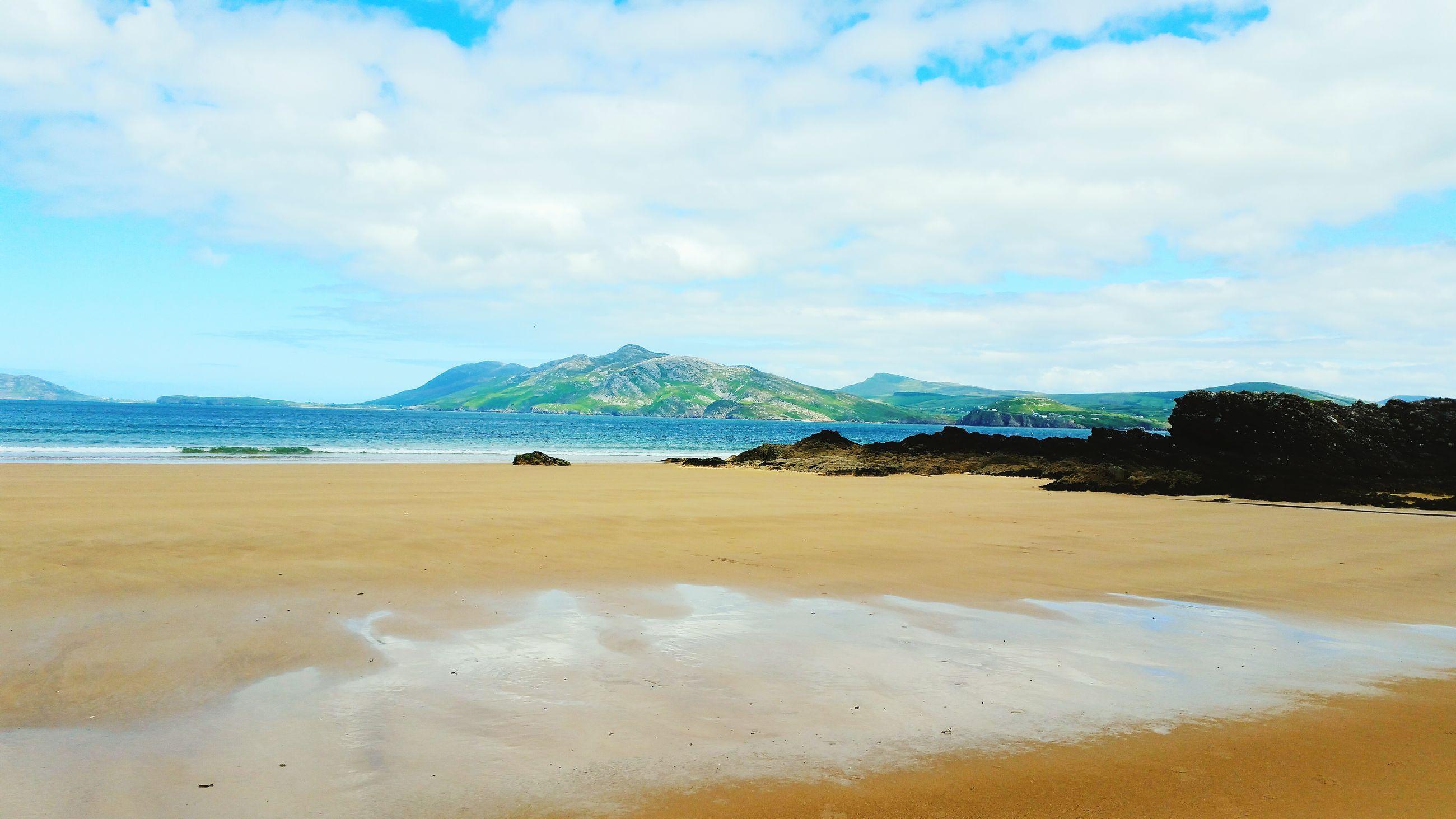 beach, sky, sand, mountain, tranquil scene, water, tranquility, scenics, sea, beauty in nature, shore, nature, cloud - sky, idyllic, cloud, mountain range, day, non-urban scene, blue, coastline