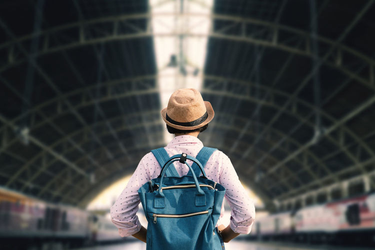 Rear view of man wearing hat standing against built structure