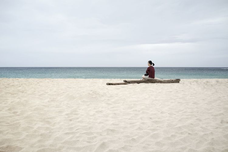 Rear view of woman sitting on driftwood at beach