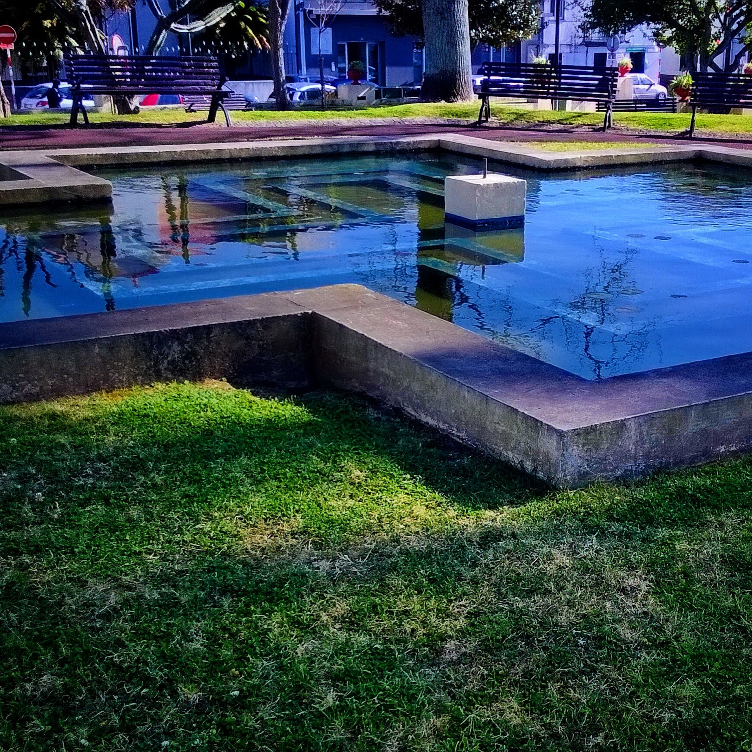 building exterior, water, architecture, built structure, grass, reflection, pond, tree, plant, park - man made space, puddle, growth, sunlight, lawn, nature, outdoors, fountain, day, green color, house