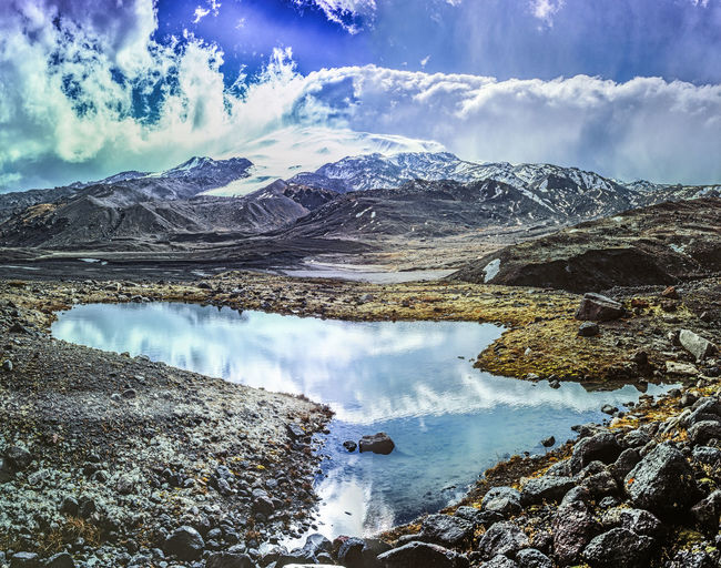 Highlights and reflections Cloudy Sky Water Stones Sun Through The Clouds Mountain Chain Snow Meditating Nature Traveling No People Environment Nature Photography Nobody Caucasus Mountains Hiking Trail Peaks Panoramic View Inspirational View Beauty In Nature EyeEmNewHere The Traveler - 2018 EyeEm Awards