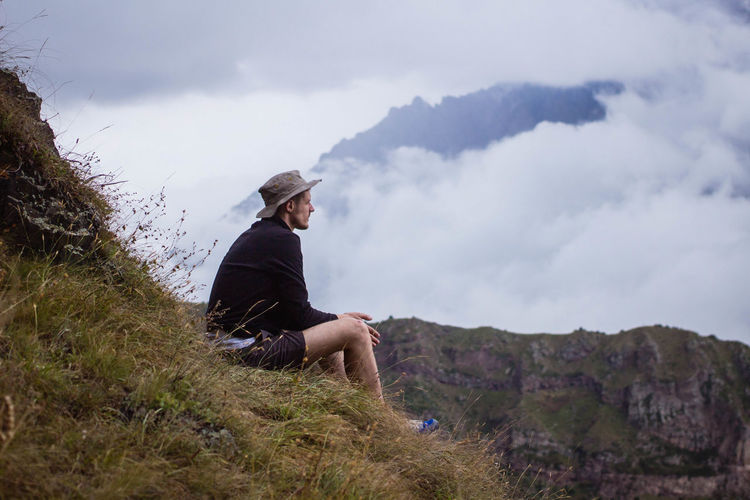Thoughtful Hiker Sitting On Grassy Hill Against Cloudy Sky
