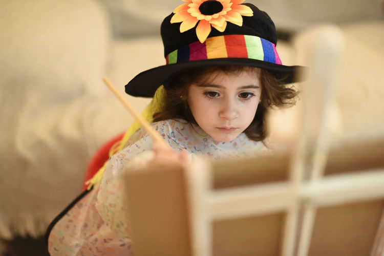 Happy little girl painting a picture at home Childhood Child Portrait Innocence One Person Cute Looking At Camera Hat Headshot Front View Girls Clothing Offspring Females Selective Focus Holding Real People Day