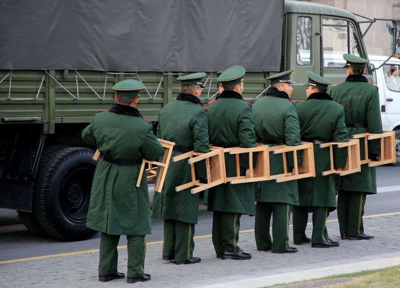 Soldiers carrying stools getting ready to march Adult Adults Only Chairs Chinese Food Day Headwear Military Truck Only Men People Sold Soldiers