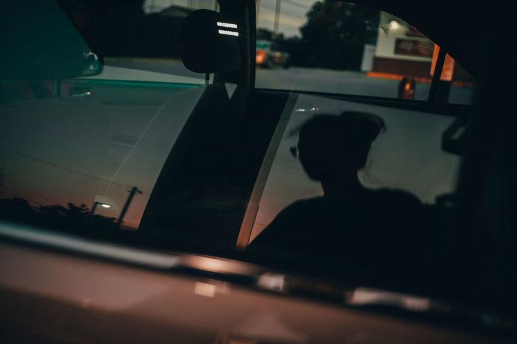 Silhouette man seen through car window