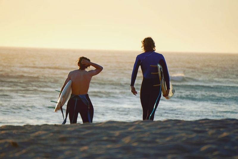 Rear View Of Male Friends Carrying Surfboards At Beach