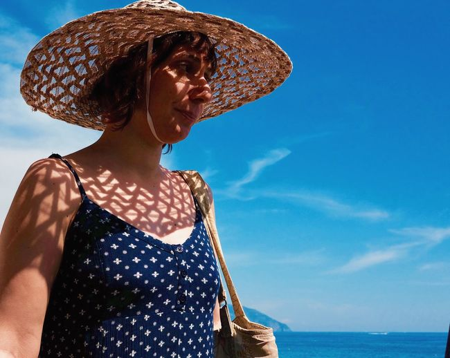 Midsection of woman wearing hat against sea against sky