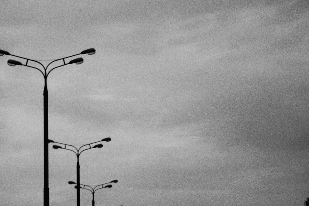 street light, sky, cloud - sky, street, low angle view, lighting equipment, nature, no people, day, technology, outdoors, electricity, silhouette, light, fuel and power generation, pole, in a row, metal, overcast