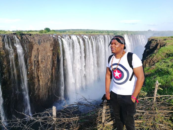 Smiling Young Man Standing Against Waterfall
