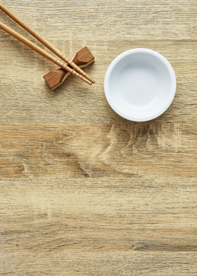 High angle view of bowl and chopsticks on rest at table