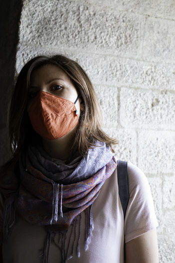 Portrait of woman covering face against wall