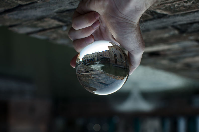 Close-up of hand holding crystal ball with buildings and canal reflection