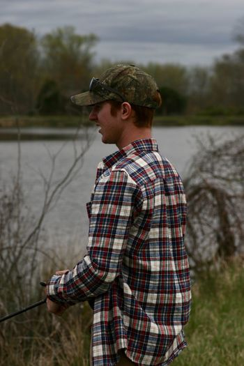 Side view of young man standing by lake