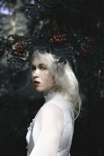 Portrait of beautiful woman standing against berry tree