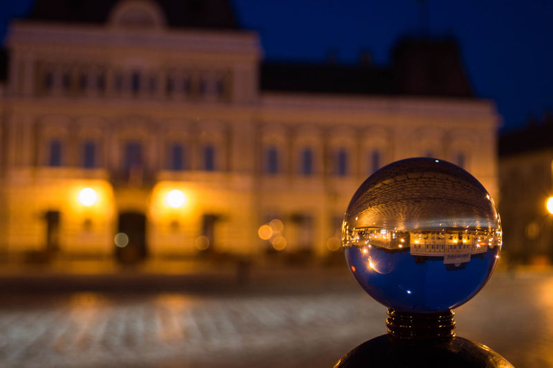 Close-up of metal sphere with reflection of illuminated building at night