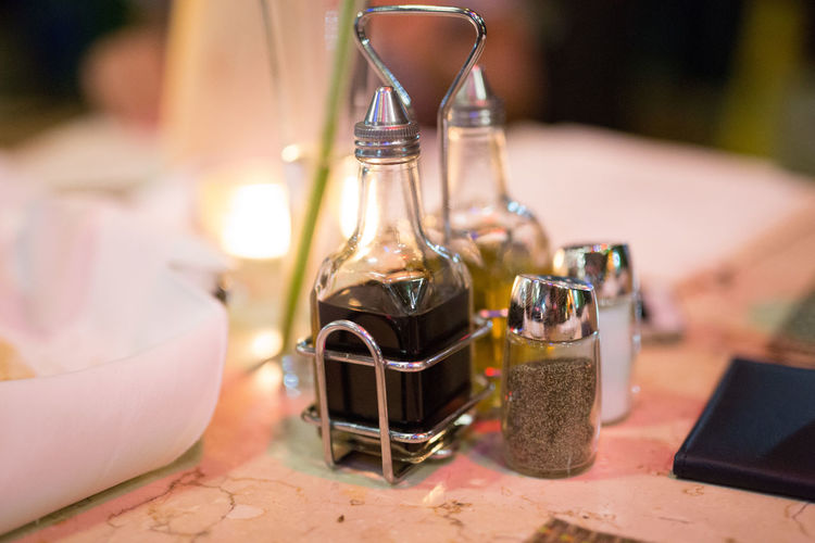 Close-up of balsamic vinegar with olive oil by salt and pepper on table