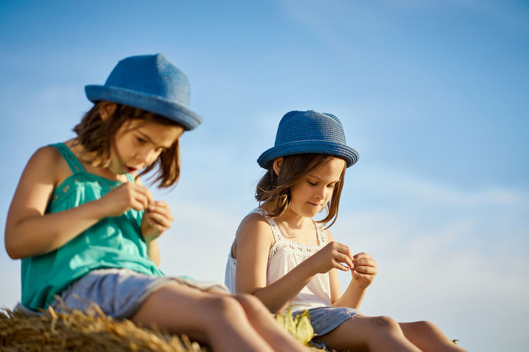 Low angle view of friends wearing hats sitting against sky