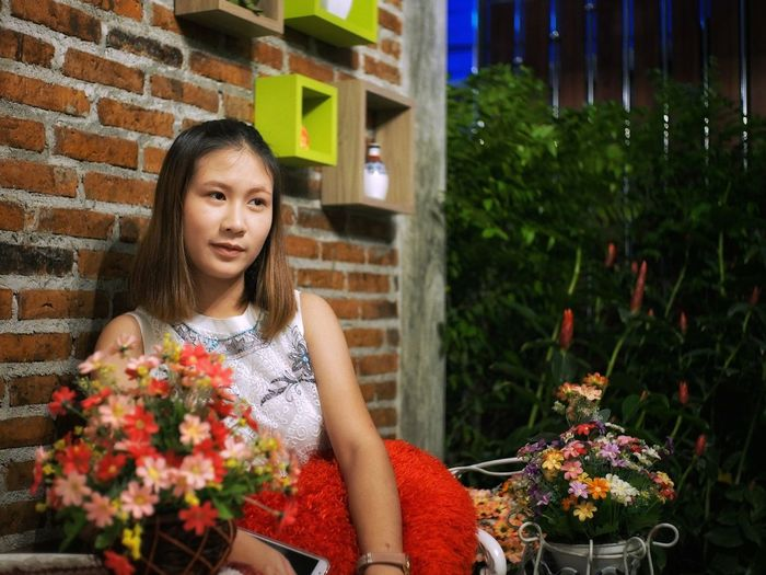 Woman looking away while sitting with flowers against brick wall