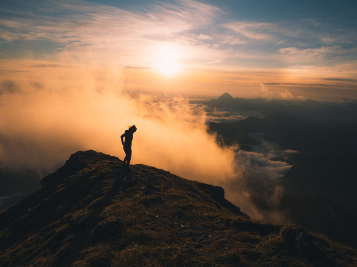 Woman standing on rock at mountain against sky during sunrise